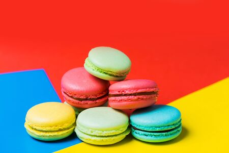 Closeup of colorful red, yellow and blue background with cake macarons