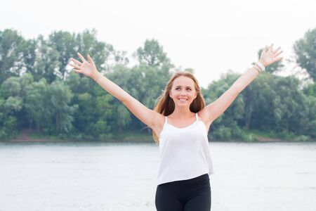 Joyful cheerful young woman raises her hands in nature and smiles. Love, happiness, positive emotions, travel, vacation concept Stock Photo