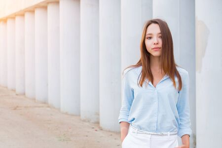 happy beautiful smiling woman outdoor on the background of the city with copy space, young student girl Stock Photo
