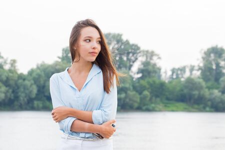 Beautiful young business woman looking away near the river and trees. Horizontal photo with copy space.