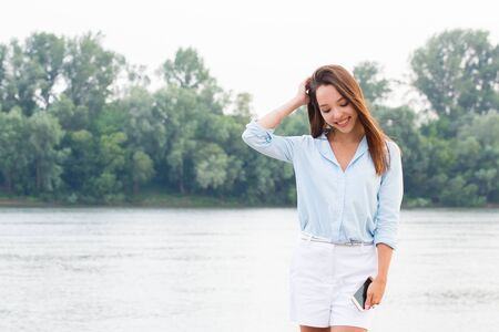 Young business woman holding a smartphone in her hand and look down at nature. Happiness, lifestyle, success of the concept Stock Photo