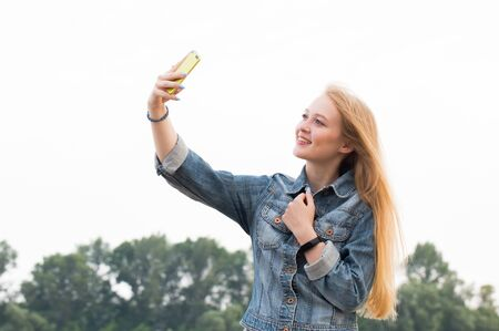 Beautiful blonde woman with long hair and in jeans with a smile makes a selfie on the background of nature and the sky Stock Photo