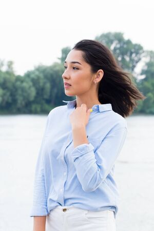 Portrait of a beautiful woman near the river. The girl dreamily looking to the side