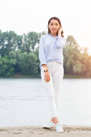 Full height portrait of beautiful brunette woman on the riverfront. Girl smiling looking at the camera