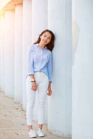A beautiful brunette woman in a blue shirt and white trousers stands near the gray columns and smiles looking to the side