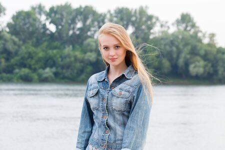 Beautiful blonde woman in blue jeans and with long hair on nature background with copy space. Young student girl looking at camera and smiling Stock Photo