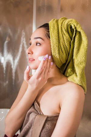 Gorgeous girl applying moisturizing cream on her face after a shower. Skin care and beauty