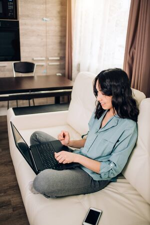 Lovely woman with pleasant appearance sits on comfortable sofa with legs crossed focused in laptop computer, surfed social networks, reads information on website. Remote work, freelance, communication