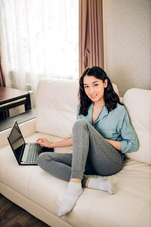 Pretty female with positive smile sits in sofa near window uses generic laptop computer and high speed internet connection, relaxed at home. Modern technology, leisure, communication concept.
