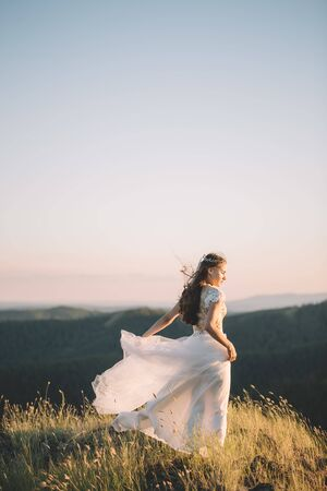 Brunette woman in white wedding dress in the wind in the mountains, side view