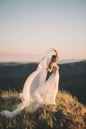 Beautiful young brunette woman in a white veil Curling in the wind and in a white dress on top of a high mountain in summer outdoors. Fine art, wedding, happiness, lifestyle, love, life concept
