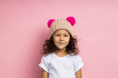 Lovely cunning little girl wearing white t shirt, knitted beige hat, looking sly and tricky, grinning mysteriously, having interesting plan or idea, standing over pink background. Facial expressions. Stock fotó