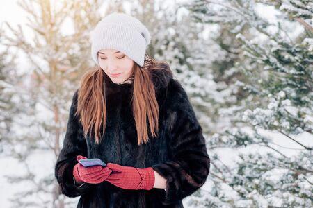 a woman using a smartphone in winter Archivio Fotografico - 137784698