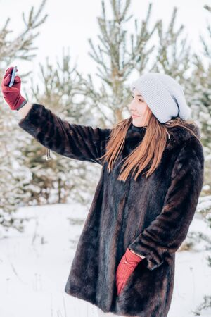 Beautiful smiling happy woman takes a selfie on her smartphone in winter Archivio Fotografico - 137793984