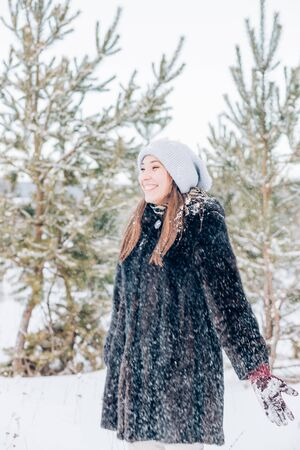 A beautiful young woman in warm clothes stands sideways in a winter forest during a snowfall and smiles, rejoicing in the weather Archivio Fotografico - 137803539