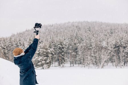 Photographer or videographer a man in a warm blue coat shoots nature on camera on the stabilizer against the background of winter forest and snow, from behind Archivio Fotografico - 138038898