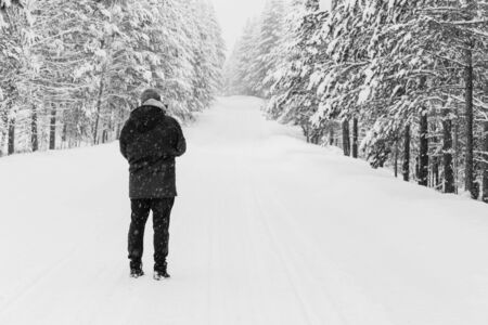 Winter black and white photo of a man standing with his back on the road in winter during a snowfall, Copy space Archivio Fotografico - 138148686
