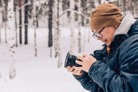 Closeup of a handsome man photographer or videographer in glasses with a camera in his hands on the background of winter nature and snow. Copy space. Archivio Fotografico - 138092242