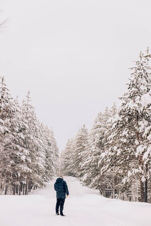 Frome behind portrait of a man in a warm jacket in the winter nature on the road against the background of tall trees and snowfall Archivio Fotografico - 138148689