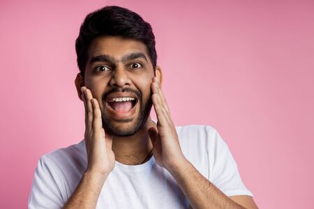 Stunned handsome unshaven indian male, being shocked by low prices on sale, keeping hands on cheeks, opening mouth in surprise, isolated over pink background. Emotions, reactions concept. Copy space. Imagens