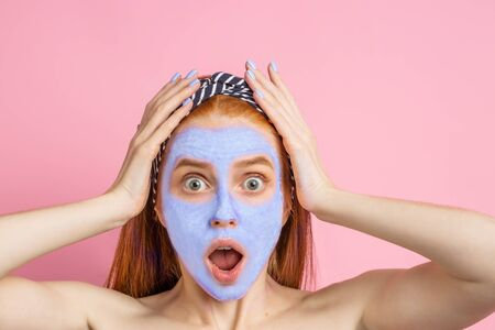 Shot of amazed shocked young caucasian redhead woman with mask or peeling gel on face, looking at camera with surprised expression and open mouth, clutching her head, posing on pink background.