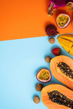 Top view of tropical fruits on orange blue background with free space for your text. Set of fresh dragon fruit, papaya, rambutan, mango, passion fruit, orange, longan, strawberry. Summer concept. Stock Photo