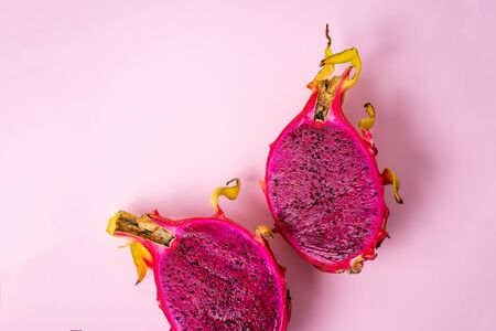 Half of fresh ripe dragon fruit isolated on pink background with copy space for your text. Summer, food concept. Horizontal shot