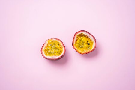 Two halves of passion fruit, maracuja isolated on pastel pink background with copy space. Selective focus. Exotic tropical fruits, food concept.