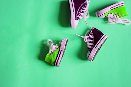 Stylish cute small green and violet baby sneakers with white laces isolated on mint color background with copy space. Miniature shoes. Top view, flat lay.