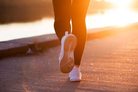 Closeup white sneaker of athlete woman runner feet on sunset background Reklamní fotografie