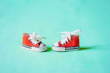 Closeup of red mini baby boots, small sneakers isolated on green background. Pair of miniature shoes for handmade dolls. Decorative element. Stockfoto