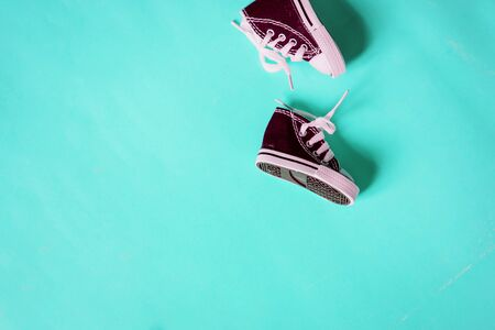 Miniature sneakers isolated on color background