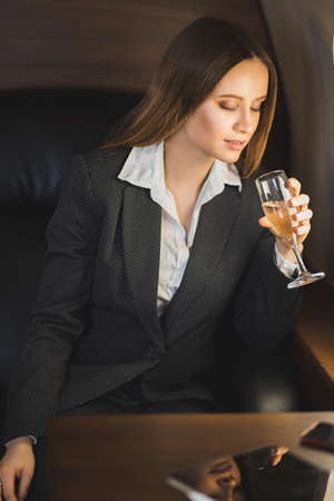A beautiful confident caucasian business lady in suit, with makeup, long hair sitting in a private jet with a glass of champagne, celebrating success. Business concept.