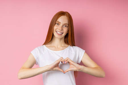 Portrait of beautiful red haired woman with freckled face, showing heart gesture, confessing in love, having romantic feelings, wearig white t shirt smiling broadly standing over pink wall.