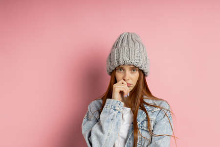 Confused puzzled carefree young caucasian ginger woman in gray knitted hat, denim jacket shrugging shoulders looking at camera with guilty and uncertain facial expression isolated pink background. Banque d'images