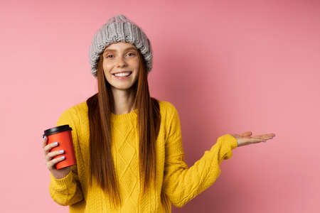 Optimistic happy girl wearing casual clothes holding copy space in one hand, disposable cup of hot drink in other hand, keeping palm open smiling posing on pink background.