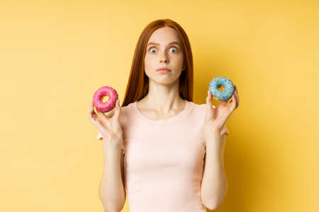 Unhappy frustrated slim ginger young woman on diet holding two color donuts, cant eat delicious confectionery, isolated over yellow background. Junk food, dieting, weight loss concept.