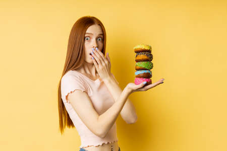 Shot of slim nice surprised caucasian redhead woman in casual t shirt holding pile of colorful donuts, looking with puzzled expression over yellow background. Bakery, unhealthy food, diet concept.