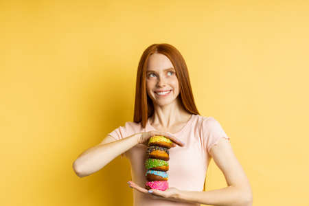 Happy joyful redhead woman sweet tooth holding pile of colorful glazed donuts, broadly smiling looking at camera standing against yellow studio wall. Pastry, bakery concept.