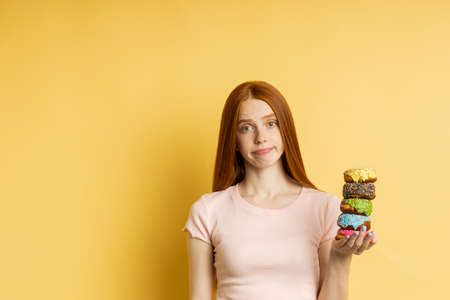 Unhappy frustrated slim ginger young woman on diet holding color delicious donuts, cant eat pastry, isolated over yellow background with copy space. Junk food, dieting, weight loss concept. Banque d'images