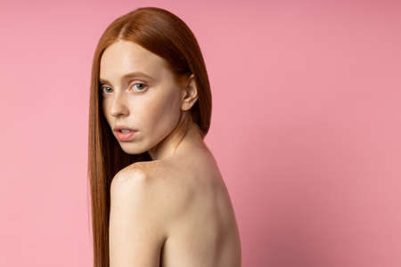 Closeup portrait of charming caucasian ginger young woman with freckles, naked shoulders, clean healthy skin, looking in camera with serious and calm expression over pink studio wall. Beauty and care