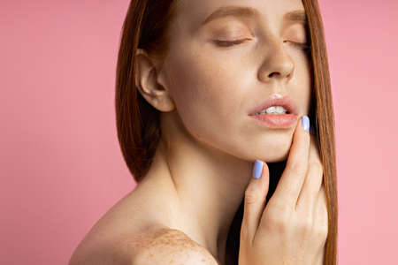 Closeup portrait of young pleased sexy naked female with red hair, clean skin, closed eyes touching neck isolated on pink background. Spa treatments and skin care concept. Banque d'images