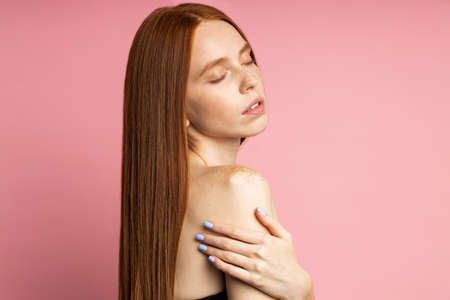 Relaxed satisfied woman after spa treatments. Studio shot of redhead caucasian female model with clean perfect skin, healthy hair posing with closed eyes over pink background. Care and beauty products