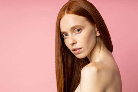 Studio portrait of sensual young woman with red long hair over pink background. Pretty naked caucasian female model with freckled fresh clean skin. Beauty and skin care concept. copy space for text.