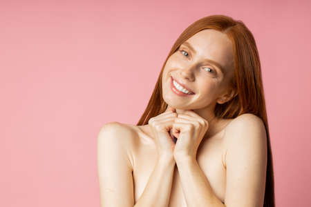 Cheerful dreamy young caucasian woman with red long hair, pure skin and naked shoulders smiling with white teeth, looking to camera over pink background. Happy girl after spa procedures.