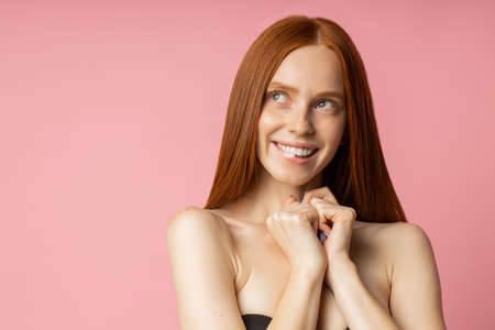 Horizontal shot of satisfied caucasian woman clenching fists with pleasure, looking aside with happy expression, broadly smiling isolated over pink background. Body care, spa, emotions concept.