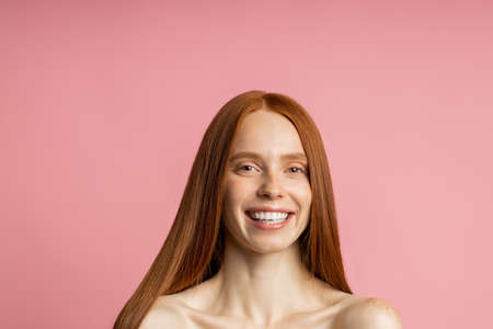 model with shiny straight long red hair. Cheerful girl with clean fresh skin pleased with hair treatment, smiling at camera posing on pink background. Keratin straightening. Spa procedures.