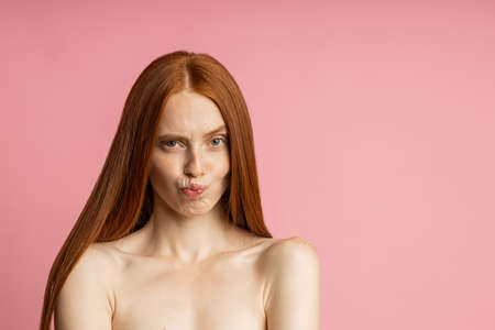 gorgeous happy caucasian redhead woman frowning eyebrows, making faces, pursing lips looking at camera standing over pink background. Facial expressions, emotions concept. Banque d'images