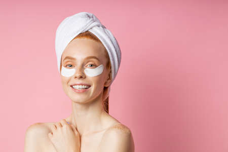 Closeup of beautiful happy caucasian woman with moisturizing under eye mask, towel on head, fresh clean skin, bare shoulders, cute smiling at camera isolated on pink background. Under eye patches.