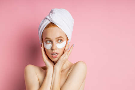 Attractive nude young African woman applying under eye patches to reduce dark circles and puffiness, keeping palms on cheeks, standing against pink background with copy space for text.